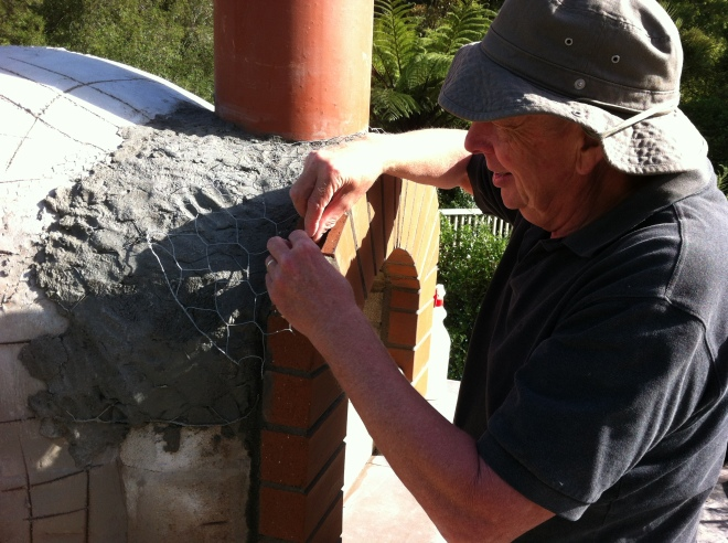 Keith adding more pig wire to prevent the plaster from cracking where it transitions from the dome to the bricks.